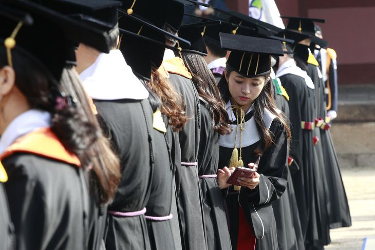 South Korean high school graduate Yoo Hye-jin checks her smartphone during a graduation ceremony at Sungkyunkwan University in Seoul, South Korea, Wednesday, Feb. 25, 2015. (AP Photo/Ahn Young-joon)