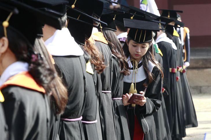 South Korean high school graduate Yoo Hye-jin checks her smartphone during a graduation ceremony at Sungkyunkwan University in Seoul, South Korea, Wednesday, Feb. 25, 2015. (AP Photo/Ahn Young-joon)