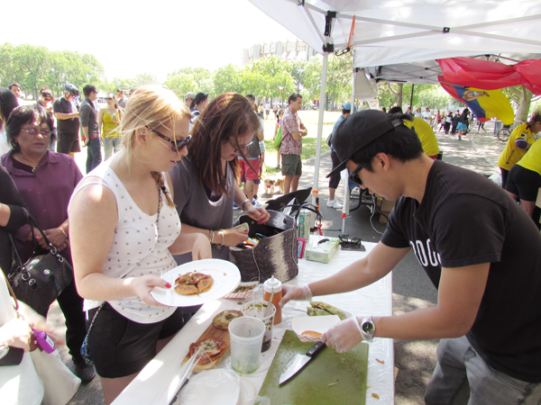 A booth worker sells kimchi jeon to customers at the World's Fair Anniversary Festival in Queens Sunday.