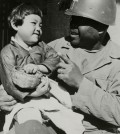 A military chaplain holds a young child in this photo taken by the International Committee of the Red Cross (ICRC) during the 1950-53 Korean War. The ICRC's Regional Delegation for East Asia released photos that provide a rare glimpse of the tragedy, Tuesday, to mark the 65th anniversary of the outbreak of the war. (Yonhap)