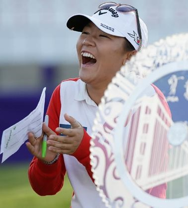 Lydia Ko of New Zealand laughs standing by her trophy after winning the Swinging Skirts LPGA Classic golf tournament Sunday, April 26, 2015, in Daly City, Calif. Ko won the tournament for the second straight year, beating Morgan Pressel on the second hole of a playoff. (AP Photo/Eric Risberg)