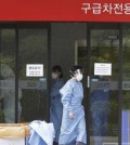 A hospital worker wears a mask as a precaution against the MERS, Middle East Respiratory Syndrome, virus as she comes out from an emergency room of Samsung Medical Center in Seoul, South Korea, Sunday, June 7, 2015. A fifth person in South Korea has died of the MERS virus, as the government announced Sunday it was strengthening measures to stem the spread of the disease and public fear.(AP Photo/Ahn Young-joon)