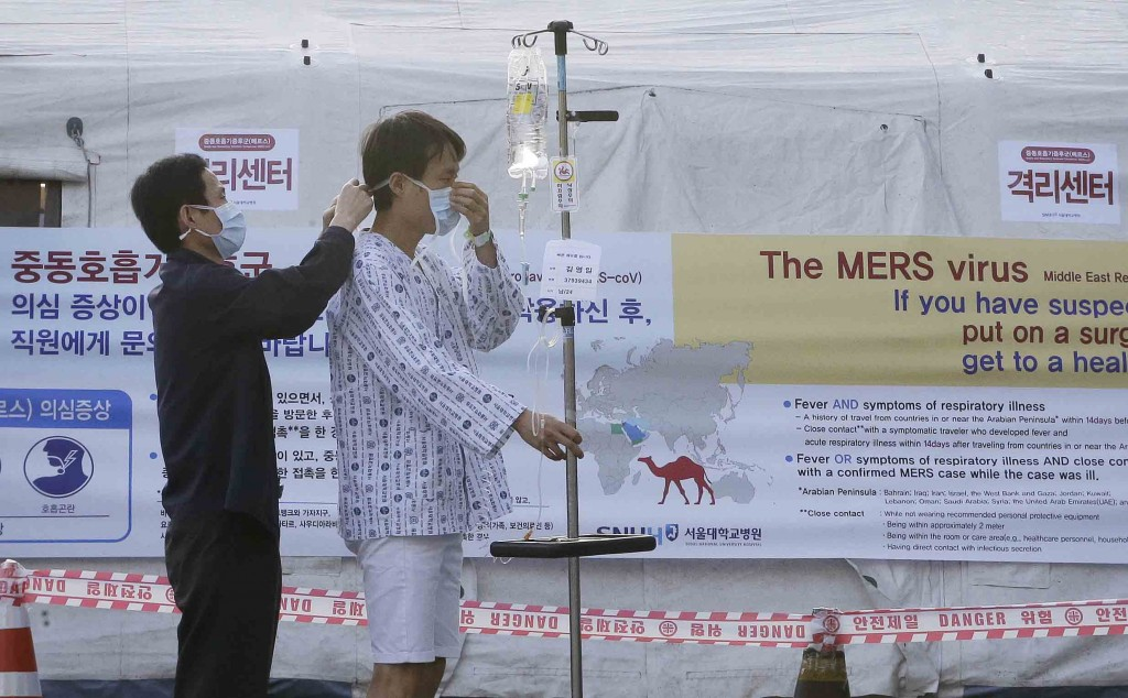 A man helps a patient to wear a mask as a precaution against the possible MERS, Middle East Respiratory Syndrome, virus in front of a facility to examine temporarily quarantined people who could be infected with the MERS virus at Seoul National University Hospital in Seoul, South Korea Monday, June 1, 2015. More than 680 people in South Korea are isolated after having contact with patients infected with the virus that has killed hundreds of people in the Middle East, health officials said Monday.(AP Photo/Ahn Young-joon)