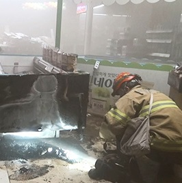 A firefighter inspects the site of a fire at Lotte Mart inside the second Lotte World in southern Seoul, Monday. (Yonhap)