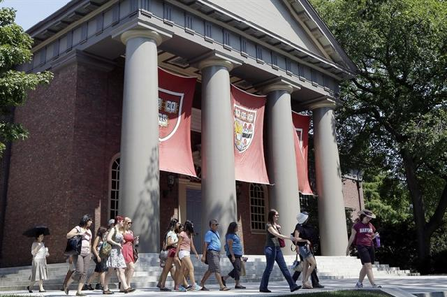 In this Aug. 30, 2012, file photo, a tour group walks through the campus of Harvard University in Cambridge, Mass. School officials said Wednesday, June 3, 2015, that Harvard Business School graduate and prominent Wall Street investor John Paulson donated $400 million to the school, its biggest gift in its history. Harvard said the endowment will support the School of Engineering and Applied Sciences, which will be renamed the Harvard John A. Paulson School of Engineering and Applied Sciences in his honor. (AP Photo/Elise Amendola