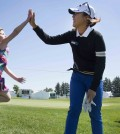 Lydia Ko, of New Zealand, gives a high-five to an enthusiastic young fan, four-year old Mackenzie Wilson after walking off the 11th hole during the pro-am at the Manulife LPGA Classic golf tournament in Cambridge, Ontario, Wednesday, June 3, 2015. (Peter Power/The Canadian Press via AP)
