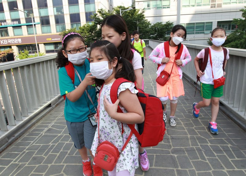 South Korean elementary school students wear masks as a precaution against the MERS, Middle East Respiratory Syndrome, virus as they go to school in Seoul, South Korea, Wednesday, June 10, 2015. South Korea believes its MERS virus outbreak may have peaked, and experts say the next several days will be critical to determining whether the government's belated efforts have successfully stymied a disease that has killed seven people and infected nearly 100 in the country.(AP Photo/Ahn Young-joon)