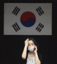 In this Thursday, June 18, 2015, file photo, an official wearing a mask as a precaution against the MERS virus works with a South Korean national flag in the background at Dongdaemun District Office in Seoul, South Korea. The head of the World Health Organization on Thursday praised beleaguered South Korean officials and exhausted health workers, saying their efforts to contain a deadly MERS virus outbreak have put the country on good footing and lowered the public risk. (AP Photo/Ahn Young-joon)