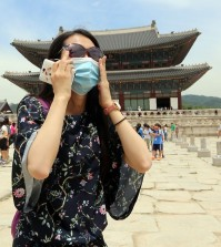 A Chinese tourist, wearing a facial mask, visits Gyeongbok Palace in Seoul on June 1, 2015, as South Korea confirmed three additional cases of the Middle East Respiratory Syndrome that day, raising the number of patients diagnosed with the illness to 18. (Yonhap)
