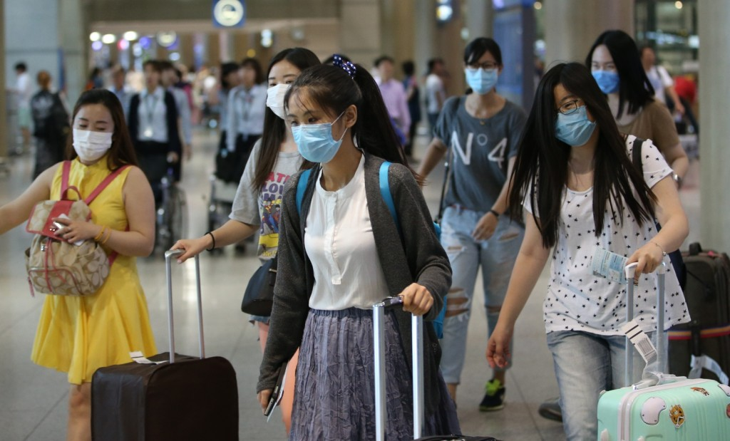 A group of foreign tourists wearing facial masks arrives at Incheon airport, west of Seoul, on June 2, 2015, as South Korea is gripped by increasing cases of the Middle East Respiratory Syndrome. The state-run Korea Tourism Organization said about 2,500 Chinese and Taiwanese tourists have called off their visits to South Korea as of June 1 due to the virus scare. (Yonhap)