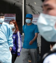 Hospital workers and visitors wearing masks pass by a precaution against the MERS, Middle East Respiratory Syndrome, virus at a quarantine tent for people who could be infected with the MERS virus at Seoul National University Hospital in Seoul, South Korea, Wednesday, June 3, 2015. South Korea on Tuesday confirmed the country's first two deaths from MERS as it fights to contain the spread of a virus that has killed hundreds of people in the Middle East.(AP Photo/Ahn Young-joon)