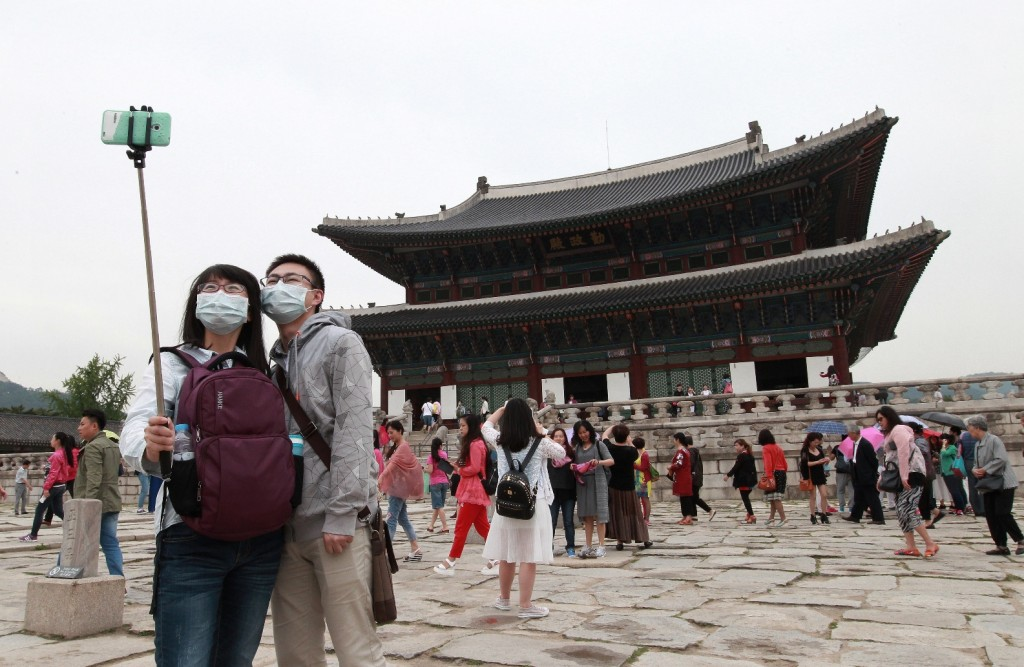 """A couple wearing masks as a precaution against the MERS (Middle East Respiratory Syndrome) virus as they take a """"selfie"""" with their smartphone at Gyeongbok Palace in Seoul, South Korea. (AP Photo/Ahn Young-joon)"""