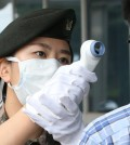 A Korean soldier checks a person for MERS symptoms (Yonhap)