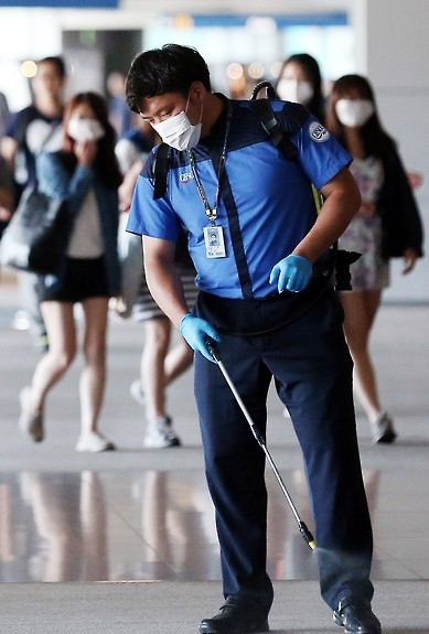 A worker sprays anti-septic solution on the arrival lobby of Incheon airport, west of Seoul, June 3, 2015, amid rising public concerns over the spread of the Middle East Respiratory Syndrome. (Yonhap)