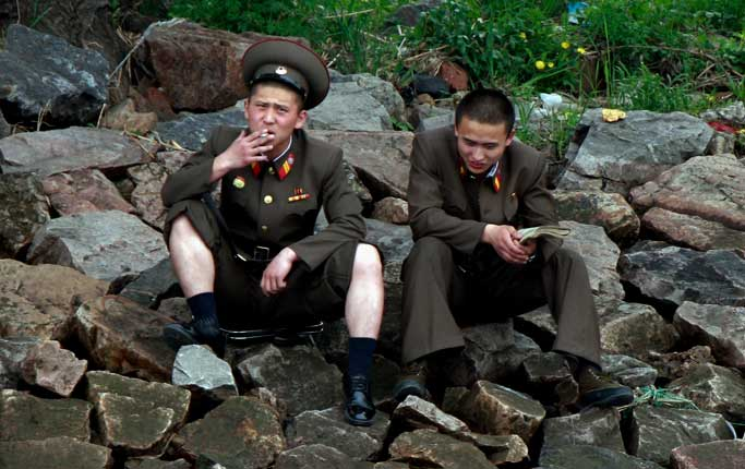 A North Korean soldier smokes a cigarette as he takes a rest with his comrade along the river bank of the North Korean town of Sinuiju, opposite the Chinese border city of Dandong Friday, May 24, 2013. A top North Korean envoy delivered a letter from leader Kim Jong Un to Chinese President Xi Jinping on Friday and told him Pyongyang would take steps to rejoin stalled six-nation nuclear disarmament talks, in an apparent victory for Beijing's efforts to coax its unruly ally into lowering tensions. (AP Photo)