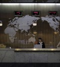 "In this Thursday, Oct. 23, 2014, file photo, a hotel staff member stands at a reception desk of a hotel, decorated with a map of the world on the wall, in Pyongyang, North Korea. Fresh off a drastic, half-year ban that closed North Korea's doors to virtually all foreigners over fears they would spread the Ebola virus - despite the fact that there were no cases of Ebola reported anywhere in Asia - the country is once again determined to show off its ""socialist fairyland"" to tourists. (AP Photo/Wong Maye-E, File)"