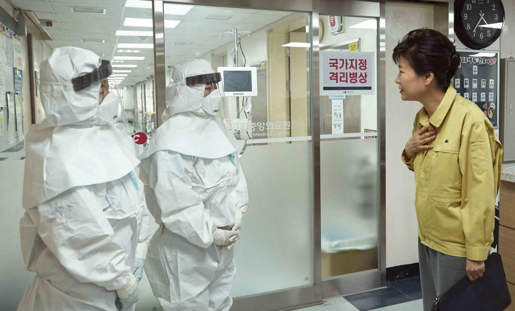 "South Korean President Park Geun-hye, right, talks with health care workers wearing protective gears as she visits the National Medical Center housing MERS, Middle East Respiratory Syndrome, patients in Seoul, South Korea, June 5, 2015. Sales of surgical masks surge amid fears of the deadly, poorly understood virus. Airlines announce ""intensified sanitizing operations."" More than 1,100 schools close and 1,600 people - and 17 camels in zoos - are quarantined. The current frenzy in South Korea over MERS brings to mind the other menacing diseases to hit Asia over the last decade - SARS, which killed hundreds, and bird flu. (Yonhap)"