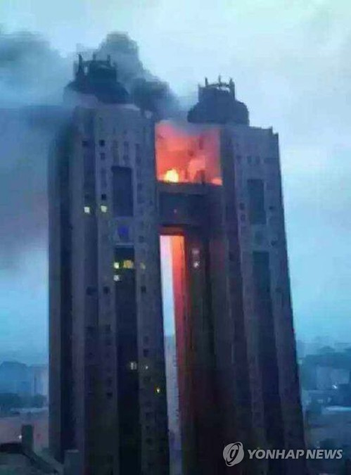 In this photo, exclusively obtained and released on June 12, 2015 by local radio station BBS, black smoke and flames billow from a bridge between the 43rd floors of Koryo Hotel in the North Korean capital of Pyongyang on the previous day. The fire had broken out at the hotel frequented by foreigners, without any information being provided on casualties or property damage, reports said on June 12, 2015. The fire appears to have been extinguished, according to The Associated Press. (Yonhap)