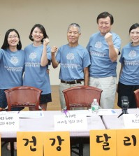 Leaders of Korean Community Services of Metropolitan New York and the Korean Road Runners Club promote upcoming three-mile marathons to raise money for a new mental health clinic.