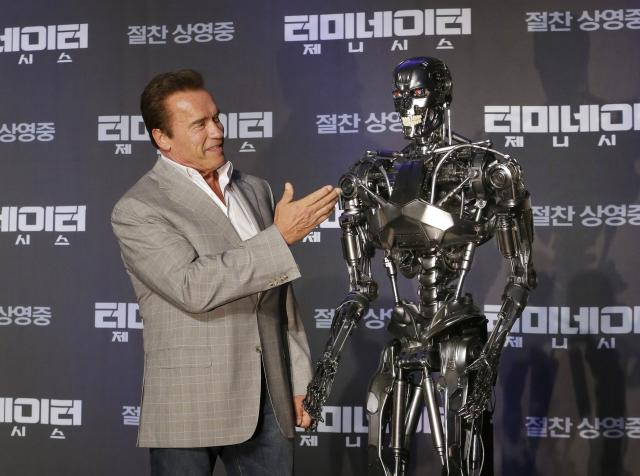 """Actor Arnold Schwarzenegger stands with a model of a """"Terminator"""" from the new film """"Terminator Genisys"""" during a press conference at the Ritz Carlton hotel in Seoul, South Korea, Thursday, July 2, 2015. (AP Photo/Ahn Young-joon)"""