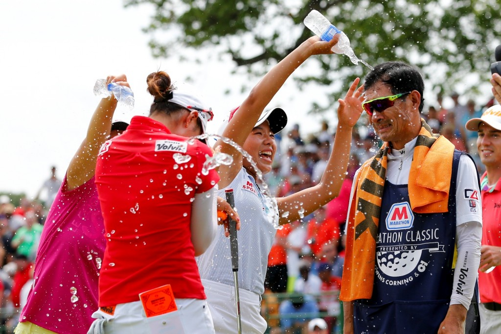 Chella Choi, front left, of South Korea, and her father and caddie Ji Yeon Choi, right, are doused by Mi Hyang Lee, also of South Korea, after winning the Marathon Classic golf tournament on the first playoff hole at Highland Meadows Golf Club in Sylvania, Ohio, Sunday, July 19, 2015. (AP Photo/Rick Osentoski)