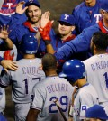 Texas Rangers' Shin-Soo Choo, center left, is congratulated by teammates after he scored on single by Robinson Chirinos during the ninth inning of a baseball game against the Colorado Rockies Tuesday, July 21, 2015, in Denver. Choo tripled in his at-bat to lead off the inning to complete the cycle. (AP Photo/David Zalubowski)