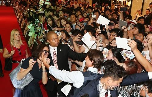 """Tom Cruise makes his way through the red carpet for """"Mission Impossible: Rogue Nation"""" in Seoul Thursday. (Yonhap)"""