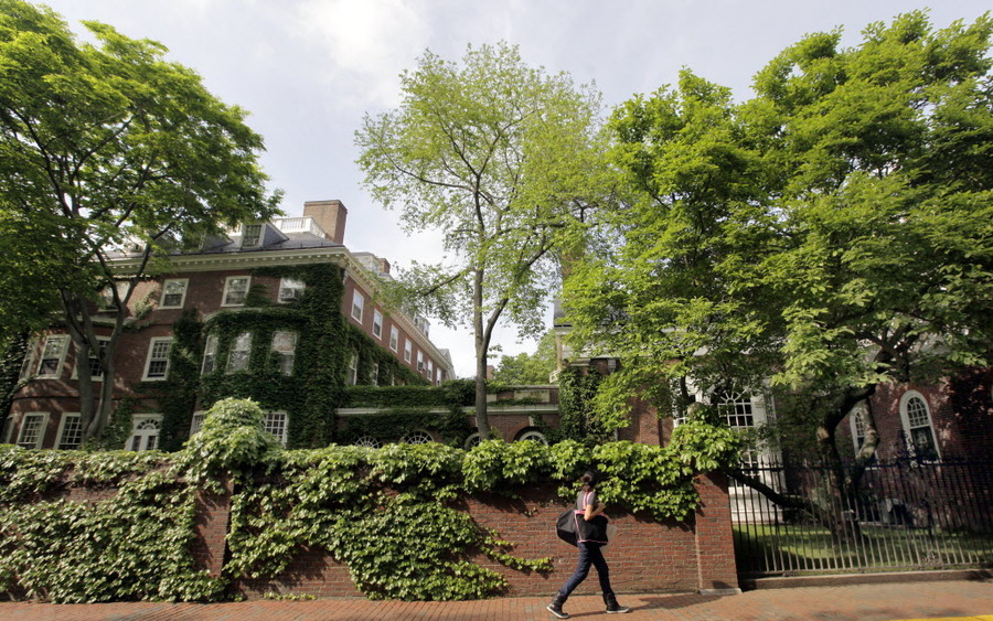 A woman walks by buildings on the campus of Harvard University in Cambridge, Mass. (AP Photo/Elise Amendola)