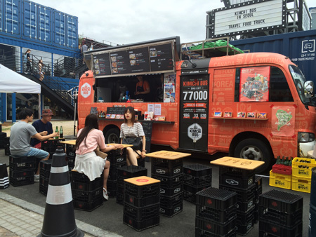Kimchi Bus customers eat its kimchi-infused Mexican dishes in front of the truck located insdie the Common Ground shopping complex in eastern Seoul. (Korea Times/Kim Bo-eun)