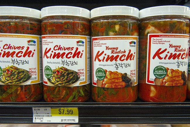 Different flavors of Korean Kimchi are displayed in a cooler at the Super H Mart Asian grocery in Fairfax, Va., Monday, July 20, 2015. Classic Korean food items are showing up with more frequency on American menus and grocery shelves. (AP Photo/Cliff Owen)