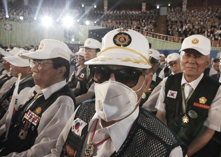 An unidentified South Korean war veteran wears a mask as a precaution against the Middle East Respiratory Syndrome (MERS) during a ceremony to mark the 65th anniversary of the outbreak of the Korean War in Seoul, South Korea, Thursday, June 25, 2015. South Korea's MERS outbreak originated from a 68-year-old man who had traveled to the Middle East, where the illness has been centered, before being diagnosed as the country's first MERS patient last month. (AP Photo/Ahn Young-joon)