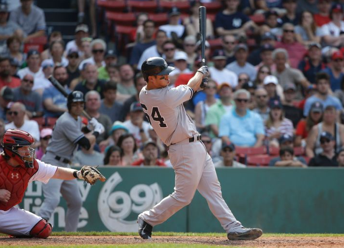 New York Yankees' Rob Refsnyder, right, hits a two-run home run as Boston Red Sox catcher Ryan Hanigan, left, looks on in the ninth inning of a baseball game at Fenway Park, Sunday, July 12, 2015, in Boston. The Yankees won 8-6.(AP Photo/Steven Senne)