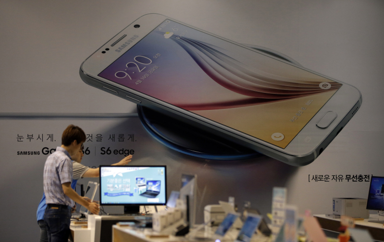Employees of Samsung Electronics Co. check the products near an advertisement of Samsung Electronics' Galaxy S6 smartphone at a Samsung Electronics shop in Seoul, South Korea, Tuesday, July 7, 2015. Samsung Electronics Co. forecast lower-than-expected profit for the April-June quarter in a sign that its much-anticipated Galaxy S6 smartphones failed to lead a meaningful recovery.(AP Photo/Lee Jin-man)
