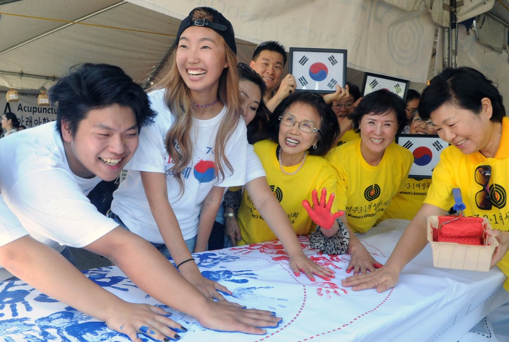 Festival goers at Seoul International Park made a Korean flag from handprints Saturday. (Park Sang-hyuk/Korea Times)