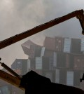 A worker stands on a crane near the site of an explosion in northeastern China's Tianjin municipality, Thursday, Aug. 13, 2015. Chinese state media reported huge explosions at the Tianjin port late Wednesday. (AP Photo/Ng Han Guan)