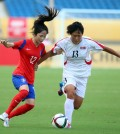 South Korea's Lee Min-ah, left, and North Korea's Wi Jung-shim fight for the ball. (Yonhap)