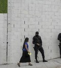 A woman walks past masked policemen guarding a street corner in San Salvador, El Salvador, Wednesday, July 29, 2015. Bus routes across San Salvador have been disrupted by a series of violent attacks and threats against those who continue to drive their routes. Since Sunday night, nine drivers have been killed, prompting authorities to increase security throughout the city. (AP Photo/Salvador Melendez)