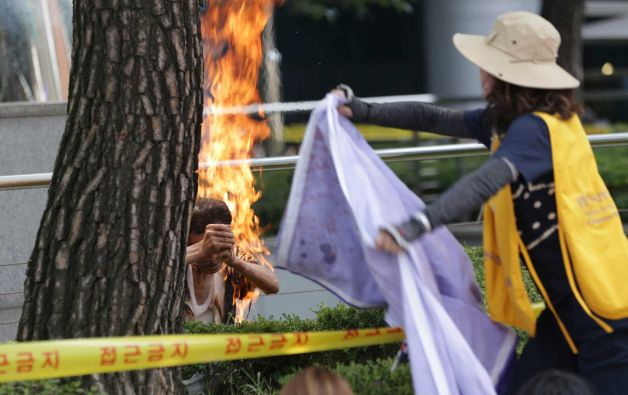 A South Korean man, left, sets himself on fire as a woman tries to extinguish him during an anti-Japan rally demanding full compensation and an apology for wartime sex slaves from the Japanese government in front of the Japanese Embassy in Seoul, South Korea, Wednesday, Aug. 12, 2015. Rescue worker Woo Kyung-suk said that the 80-year-old man sustained third-degree burns on his upper body and arms and was breathing when he was carried into an emergency vehicle. The man's motives weren't immediately clear. (AP Photo/Lee Jin-man)