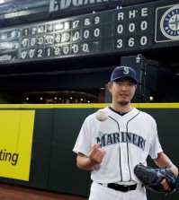 Seattle Mariners starting pitcher Hisashi Iwakuma tosses a baseball as he poses for a photo in front of the manual scoreboard at Safeco Field after he threw a no-hitter against the Baltimore Orioles in a baseball game Wednesday, Aug. 12, 2015, in Seattle. The Mariners won 3-0. (AP Photo/Ted S.)