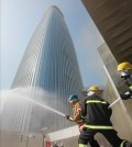 In the file photo taken on April 23, 2015, firefighters spray water in front of Lotte World Tower, a 123-story skyscraper, in Seoul's Songpa Ward, as they conduct a firefighting drill. Prosecutors said on Aug. 10, 2015, they have indicted Lotte Engineering & Construction Co. over poor construction management of the building. (Yonhap)