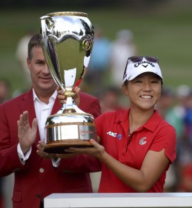 Lydia Ko, of New Zealand, holds up her trophy after defeating Stacy Lewis, of the United States, in a playoff at the Canadian Pacific Women's Open golf tournament at Vancouver Golf Club in Coquitlam, British Columbia, on Sunday, Aug. 23, 2015. (Jonathan Hayward/The Canadian Press via AP)