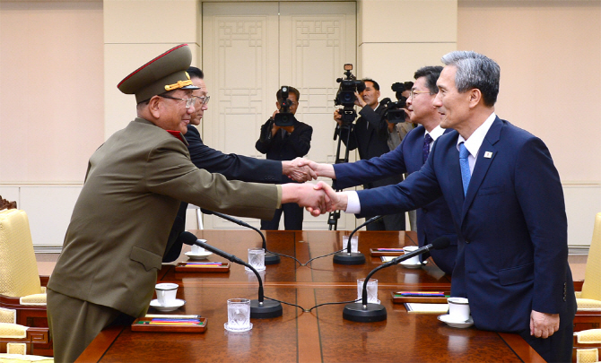 In this Aug. 22, 2015 file photo provided by the South Korean Unification Ministry, South Korean National Security Director, Kim Kwan-jin, right, and Unification Minister Hong Yong-pyo, second from right, shake hands with Hwang Pyong So, left, North Korea' top political officer for the Korean People's Army, and Kim Yang Gon, a senior North Korean official responsible for South Korean affairs, during their meeting at the border village of Panmunjom in Paju, South Korea.  (The South Korean Unification Ministry via AP)