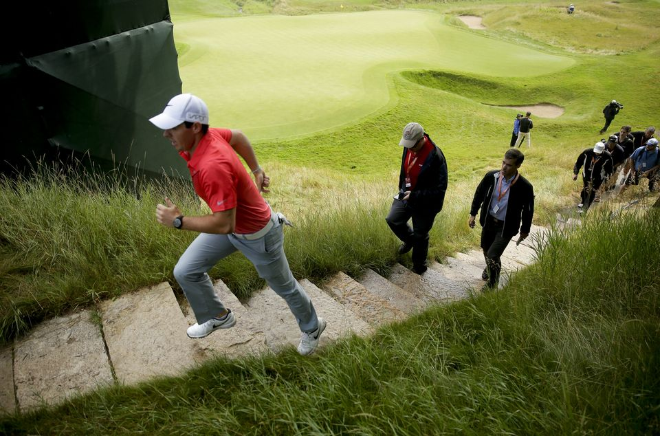 Rory McIlroy, of Northern Ireland, jogs off the18th green after a practice round for the PGA Championship golf tournament at Whistling Straits Golf Course on Monday, Aug. 10, 2015 in Haven, Wis. (AP Photo/Chris Carlson)