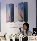 An employee of Samsung Electronics Co. watches a mobile phone near an advertisement of Samsung Electronics' Galaxy S6 and S6 Edge smartphone at a Samsung Electronics shop in Seoul, South Korea, Thursday, July 30, 2015. Samsung Electronics reported Thursday a fifth straight drop in quarterly earnings as the Galaxy S6 failed to reverse its declining fortunes in the smartphone industry. (AP Photo/Ahn Young-joon)