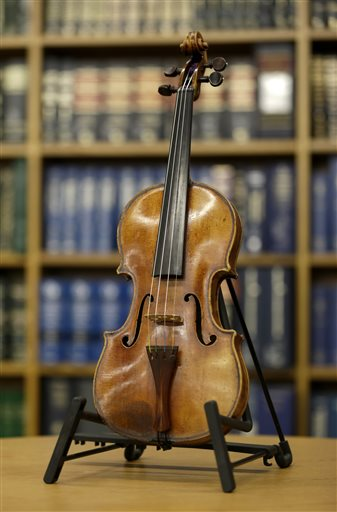 An Ames Stradivarius violin is displayed during a news conference in New York, Thursday, Aug. 6, 2015. The instrument was stolen from renowned violinist Roman Totenberg 35 years ago when he left his beloved Stradivarius in his office while greeting well-wishers after a concert in 1980. According to court documents, a woman voluntarily returned the violin to the Totenberg family and told investigators she did not know it was stolen. (AP Photo/Seth Wenig)