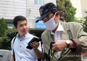 An arrest warrant was issued for a former lawmaker and husband of President Park Geun-hye's cousin, identified only by his surname Yoon (R). Yoon is suspected of receiving bribes from a then suspect who was involved in a corruption case. In the photo, Yoon walks past a reporter after a hearing at the Uijeongbu District Court on Aug. 19, 2015. (Yonhap)