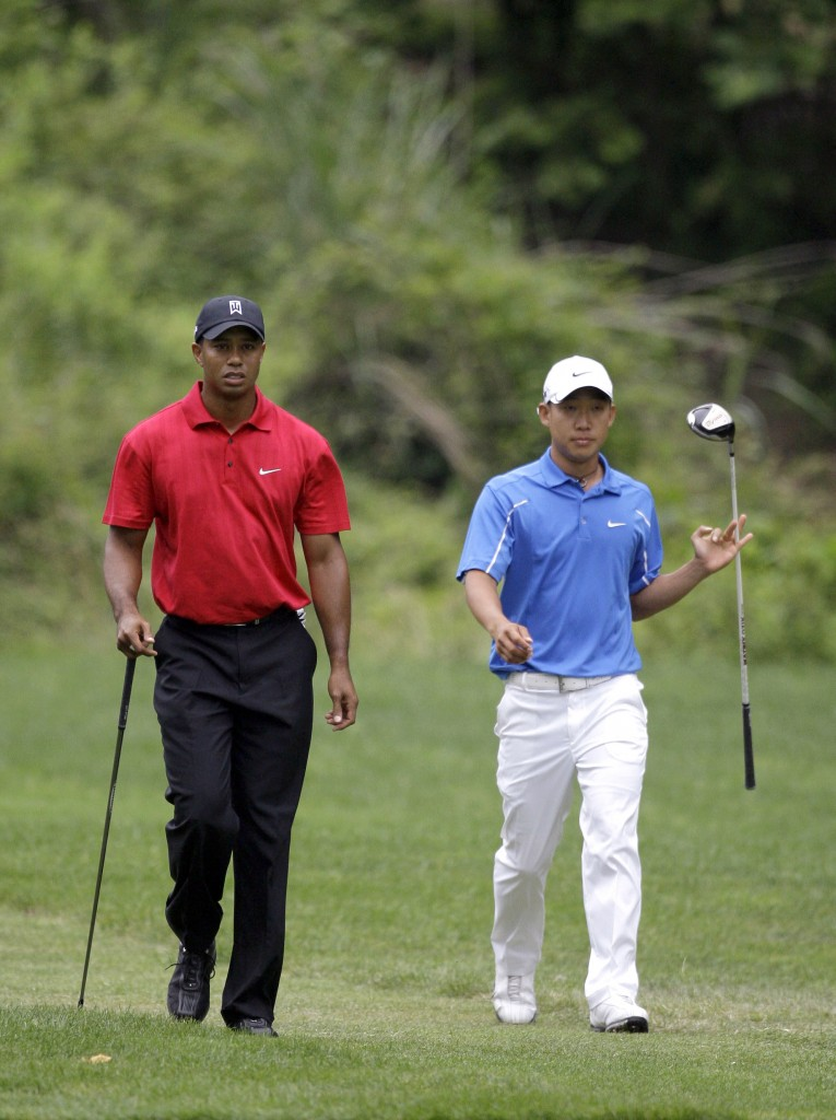 Tiger Woods, left, and Anthony Kim, right, walk down the 11th fairway during the final round of the AT&T National golf tournament at Congressional Country Club, Sunday, July 5, 2009, in Bethesda, Md. (AP Photo/Rob Carr)