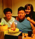 Hun Joon Lee, center, with his parents Lee Sang-sik, left, and Lee Eun-ha, right, celebrating his 15th birthday.