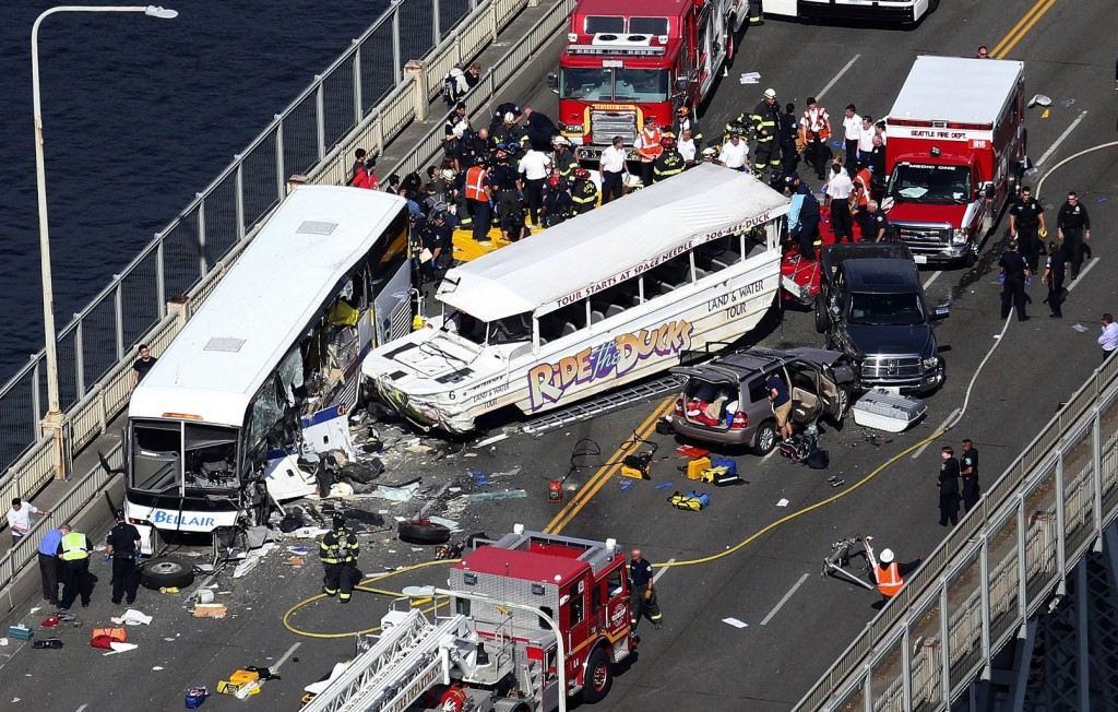 """Emergency personnel work at the scene of a fatal collision involving a charter bus, center left, and a """"Ride the Ducks"""" amphibious tour bus on the Aurora Bridge in Seattle on Thursday, Sept. 24, 2015. (Ken Lambert/The Seattle Times via AP)"""