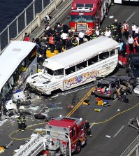 "Emergency personnel work at the scene of a fatal collision involving a charter bus, center left, and a ""Ride the Ducks"" amphibious tour bus on the Aurora Bridge in Seattle on Thursday, Sept. 24, 2015. (Ken Lambert/The Seattle Times via AP)"